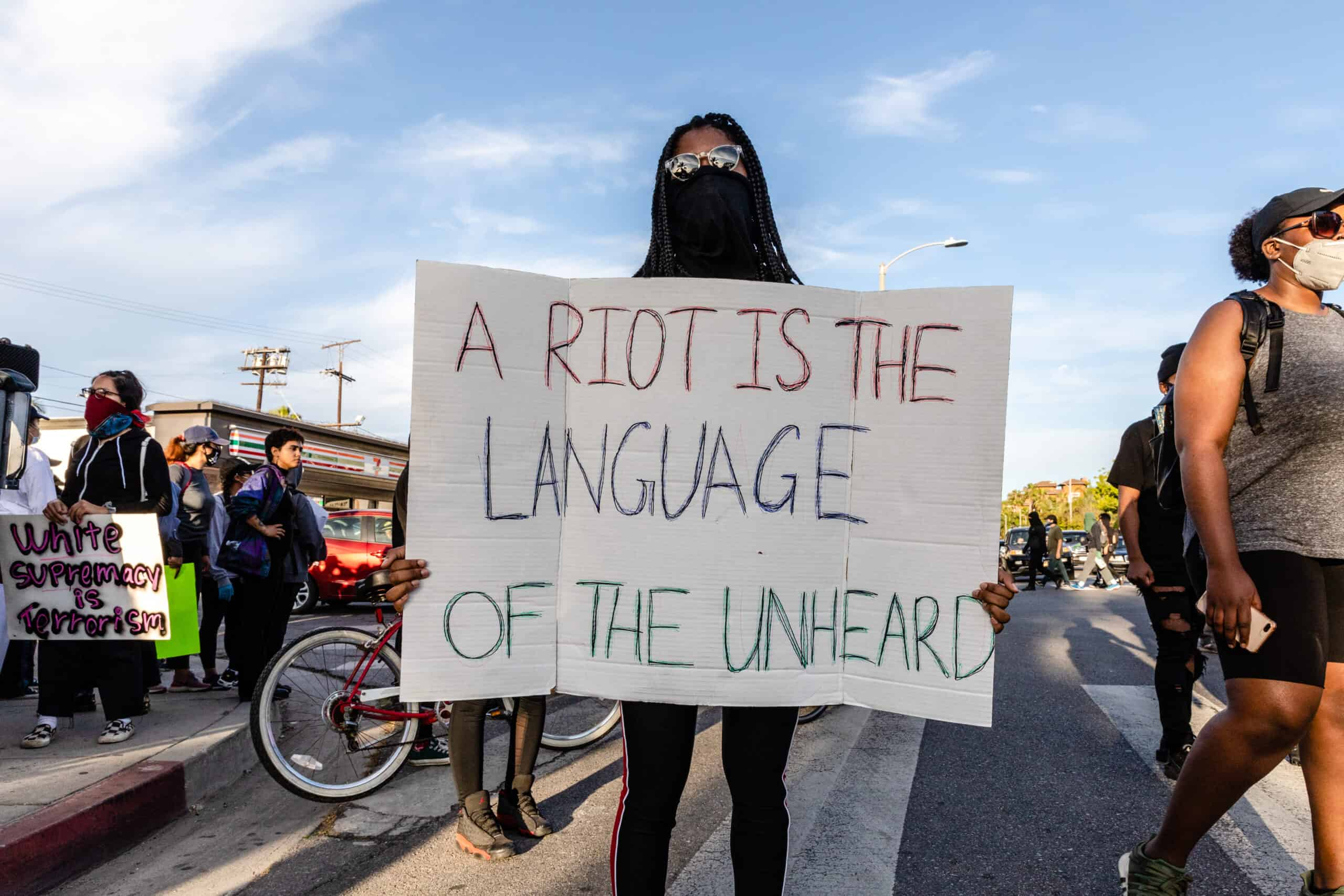 Protestor holding sign that says A Riot is the Language of the Unheard