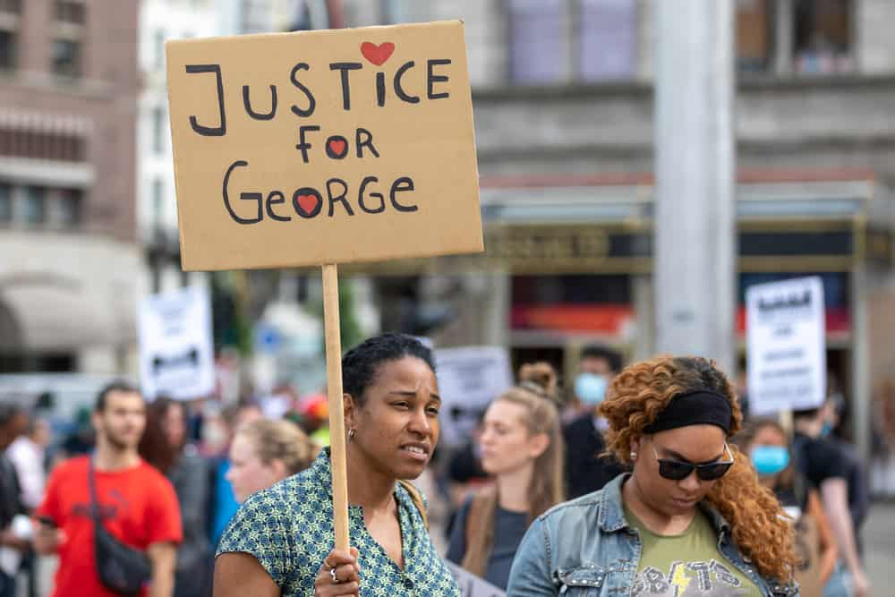 """Woman holding a sign that says """"Justice for George"""""""