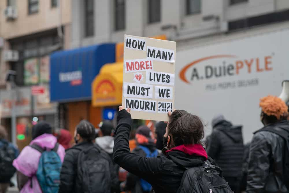 """Protestor holding a sign that says """"How Many More Lives Must We Mourn?"""""""