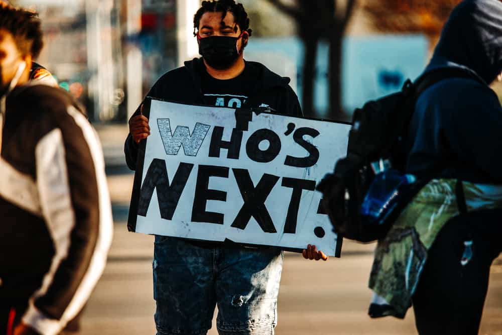 """Protestor holding a sign that says """"Who's Next"""""""