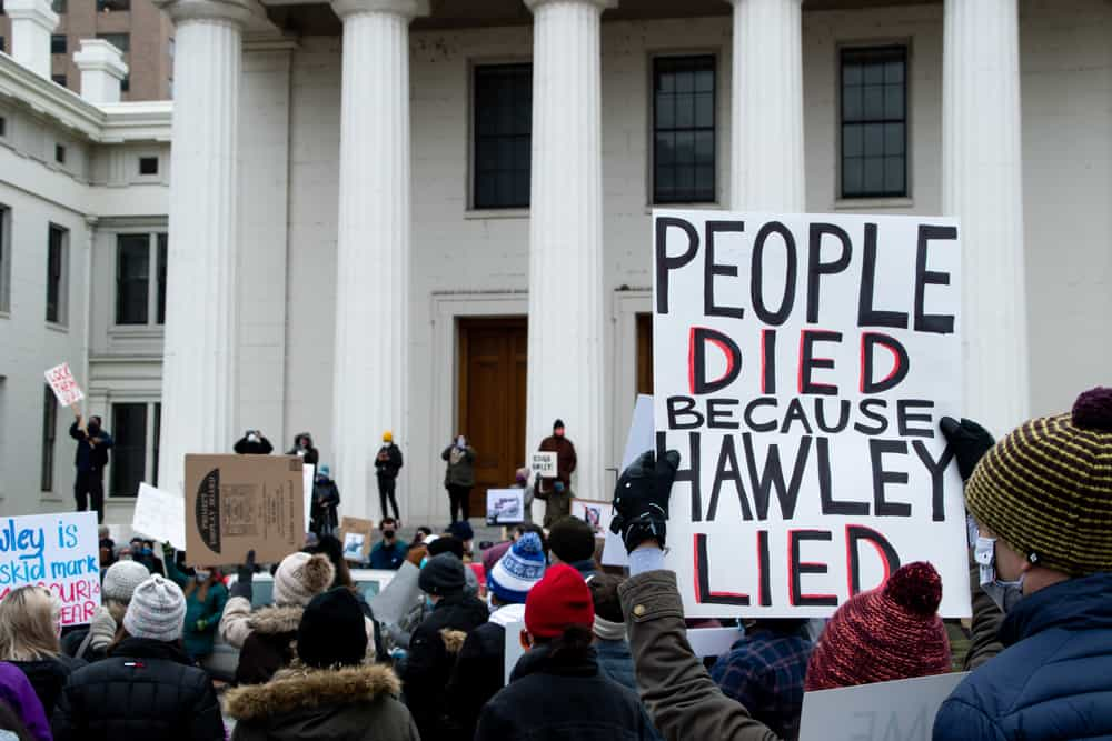 """Sign being held up stating """"People died because Hawley Lied"""""""