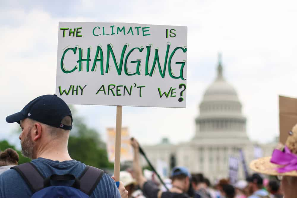 """Man holding a sign saying """"The Climate is Changing, Why aren't we?"""""""