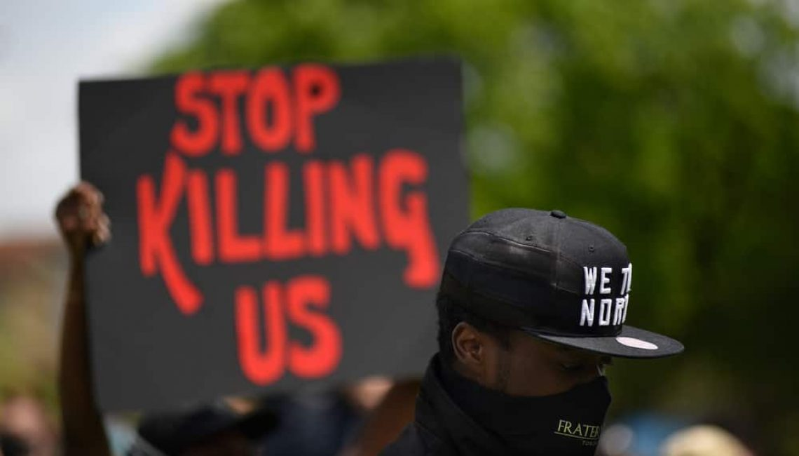 Protestor holding a sign saying Stop Killing Us